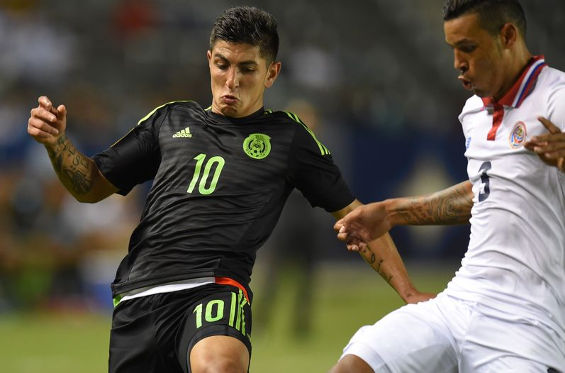 The Mexican player Victor Guzman (10) is marked by the Costa Rican July Cascante game played tonight in the United States. (AP)