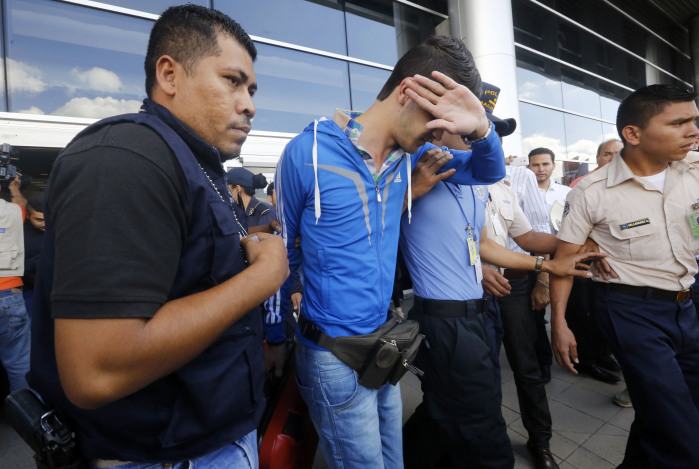Honduran policemen escort one of five Syrian citizens arrested at the Tocontin international airport in Tegucigalpa on November 18, 2015. Honduran authorities have arrested five Syrians intending to make it to the United States with stolen Greek passports, triggering alarm Wednesday in the wake of the Paris attacks launched by Syria-linked jihadists. AFP PHOTO / STR