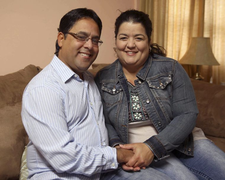 Esperanza Sosa Valdes and Ariel Del Sol Perez hold hands together in the living room of their home in Hastings. The couple escaped their home country of Cuba through Ecuador, Central America and Mexico into the United States. (Independent/Andrew Carpenean)