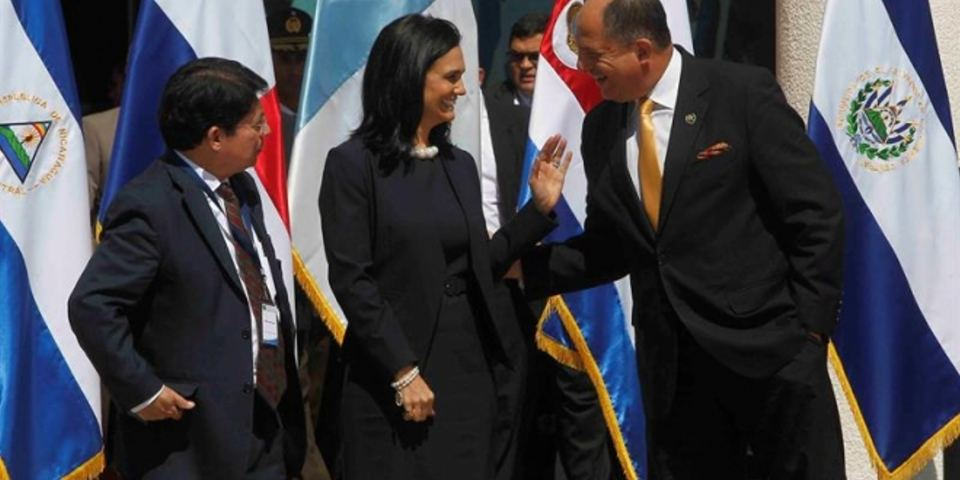 In El Salvador, President Luis Guillermo Solis exchanges words with Panama's vice-president, Isabel De Saint Malo, while Nicaragua's deputy foreign minister, Dennis Moncado, looks on.