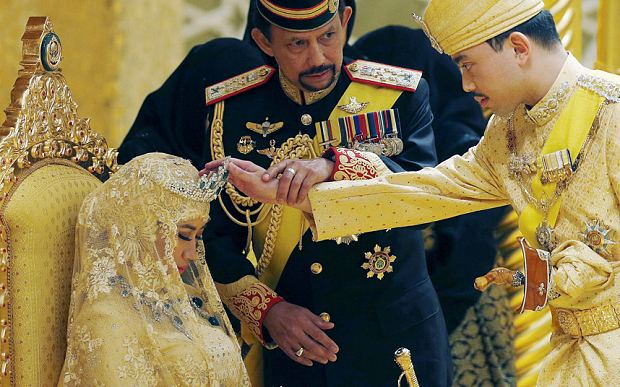Brunei's Sultan Hassanal Bolkiah holds the arm of his son Prince Abdul Malik to bless Malik's new wife Photo: Olivia Harris/Reuters