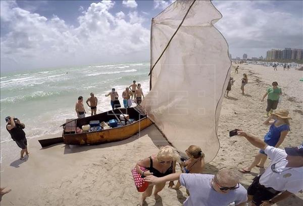 """Several people inspect a raft found on the shore at Miami Beach, Florida, and from which 14 Cuban immigrants set foot on U.S. soil and were therefore allowed to remain in the country under the Cuban Adjustment Act's """"wet food, dry foot"""" policy - a privilege that many on the island fear will soon end due to renewed diplomatic relations between the two countries. EFE/File"""
