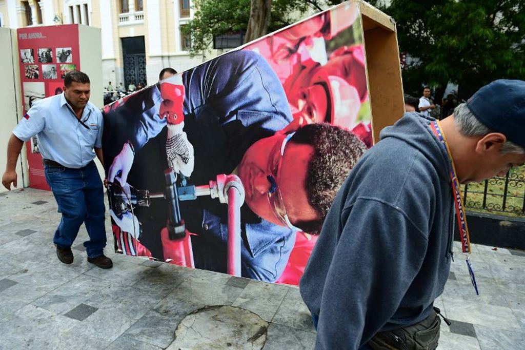 """Venezuelan National Assembly employees remove from the building  pictures of late President Hugo Chavez, in Caracas on January 6, 2016. Venezuela's opposition on Tuesday broke the government's 17-year grip on the legislature and vowed to force out President Nicolas Maduro despite failing for the time being to clinch its hoped-for """"supermajority."""" AFP PHOTO/RONALDO SCHEMIDT / AFP / RONALDO SCHEMIDT"""