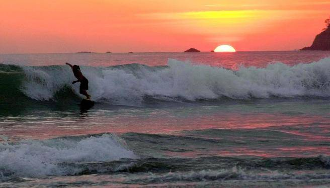 """A surfer catches a wave at sunset on a beach in Costa Rica. """"At sundown, everyone on the beach cheers the sunset, and a dozen teenage boys claim enough space to play soccer in the sand,"""" writes Jim Meek. (KENT GILBERT / AP)"""