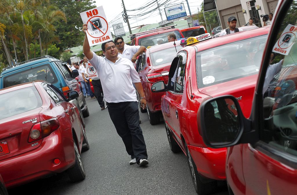 A taxi driver holds a sign which reads
