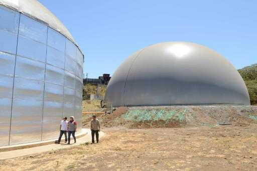 People walk past an 8,000 cubic-meter biodigestor at El Arreo slaughterhouse in Belen, Costa Ric