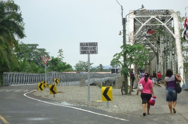 The Sixaola river crossing today: the Bailey bridge (left) allows the passage of one vehicle at a time, while the old structure, originally a railroad bridge more than a century old, allows passage for pedestrians. Photo Yessica Salazar, La Nacion