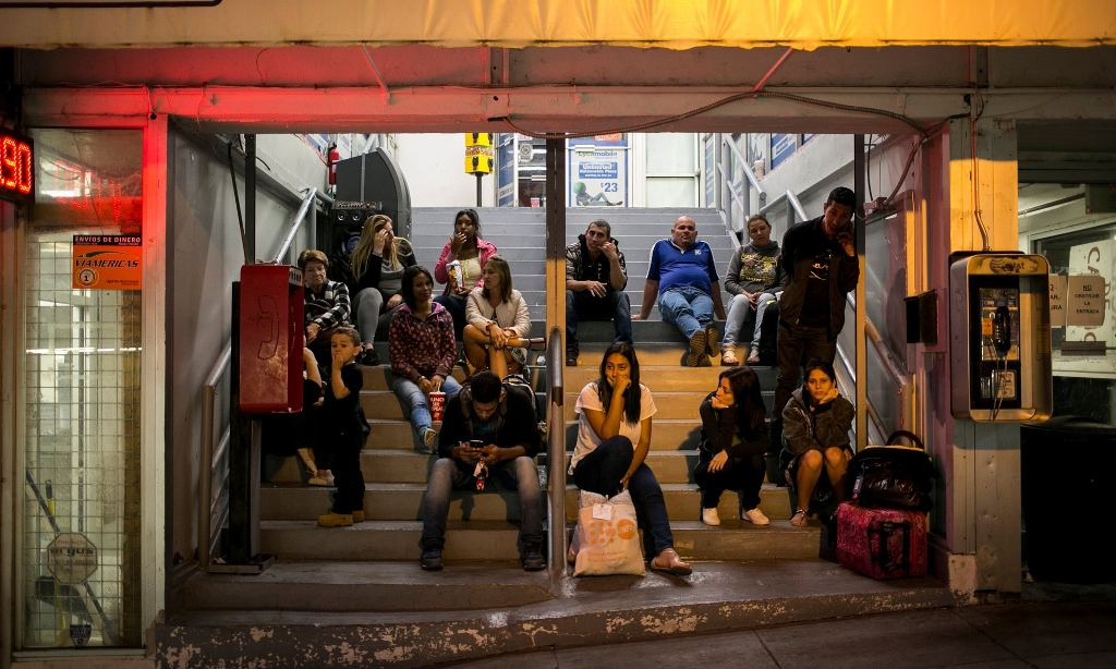 Cubans wait on the steps of Cubanos en Libertad for family members to pass through the port of entry in Laredo, Texas. Photograph: Ilana Panich-Linsman/New York Times/Redux /eyevine