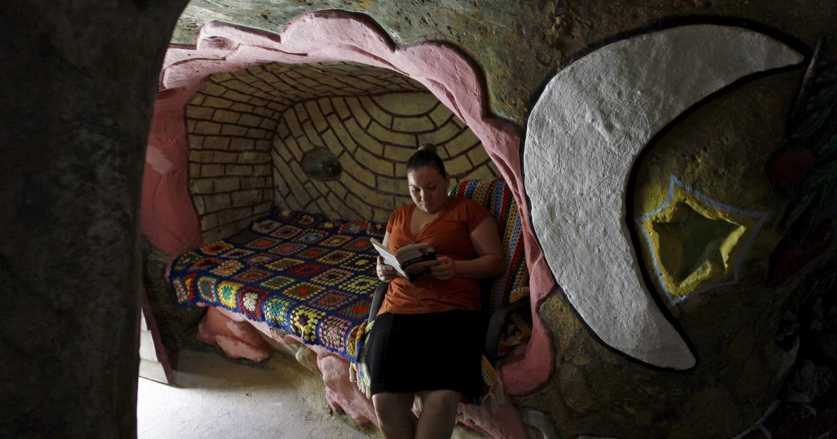 Lidieth Barrantes reads a book in one of the rooms of the house that her father built underground in San Isidro de Perez Zeledon, Costa Rica, March 14, 2016. The dwelling, which Barrantes says provides a peaceful and comfortable home for him and his family away from noise pollution and the effects of climate change, now covers about 2,000 square feet.  Photo Juan Carlos Ulate/Reuters