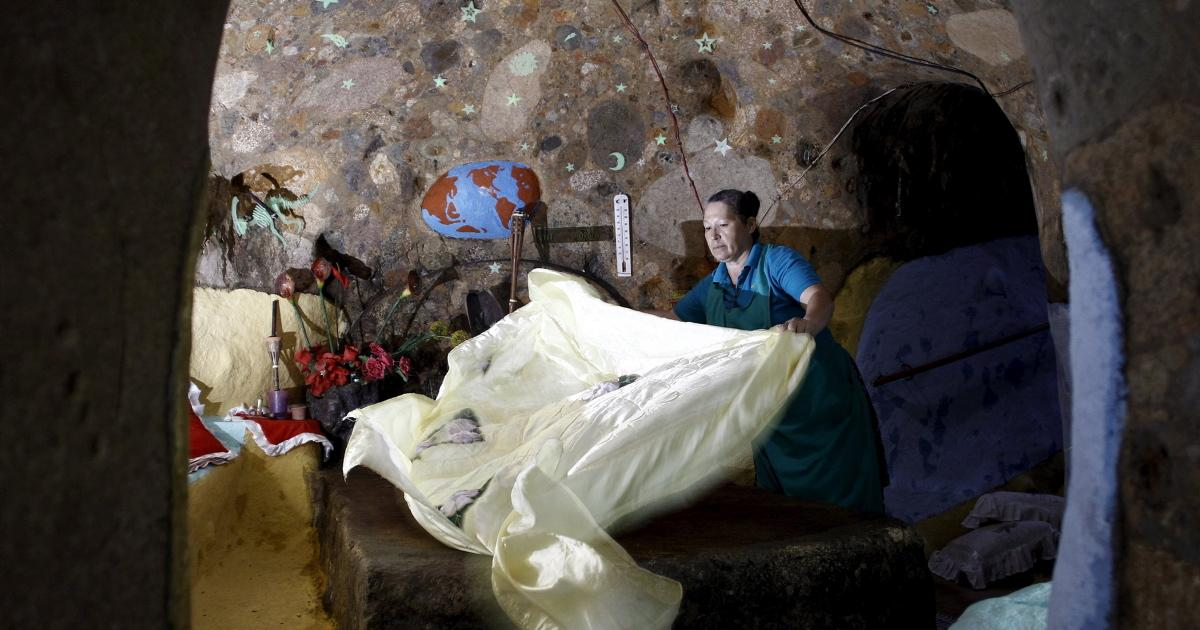 Cristal Barrantes makes a bed in her bedroom at the house that her husband Manuel Barrantes built underground in San Isidro de Perez Zeledon, Costa Rica, March 14, 2016. Photo Juan Carlos Ulate/Reuters