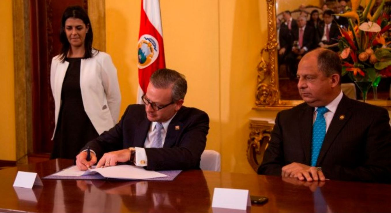 Foreign Minister Manuel Gonzalez signing the declaration on Thursday at Casa Amarilla. President Luis Guillermo Solis, o this left, looks on.