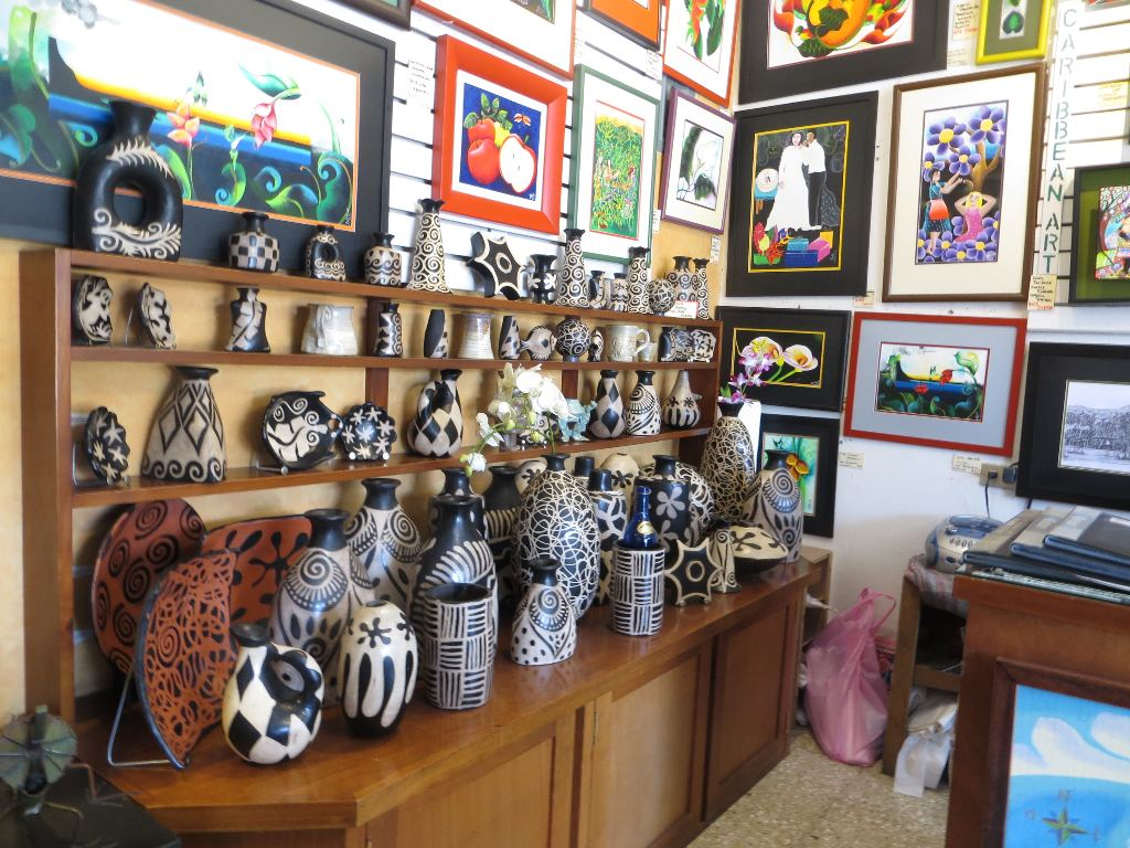 These shelves exhibit traditional women's pottery from the Lenca tribe from Honduras. The paintings on the wall are folk art from the campesinas (the farming women) from the Arenal Volcano region, in Costa Rica.