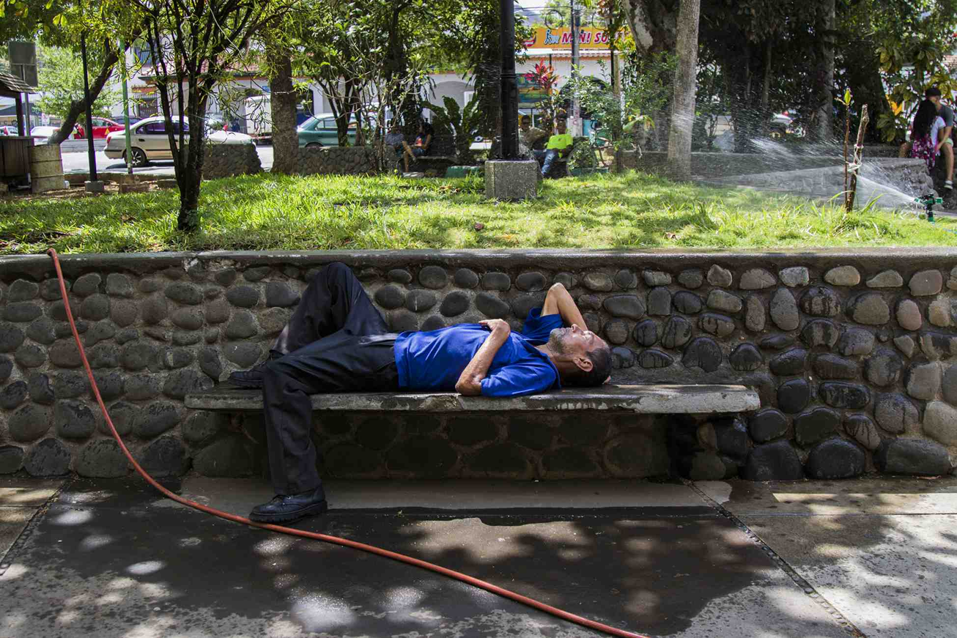 During the morning in March, a homeless man sleeps next to the water sprinklers in Recaredo Briceño park in Nicoya. Photo Ariana Crespo