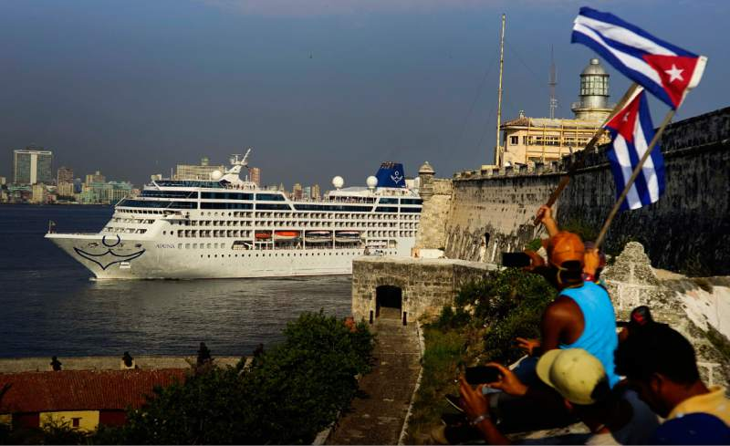 People waving Cuban flags greet passengers on Carnival's Adonia cruise ship as they arrive from Miami in Havana, Cuba, Monday, May 2, 2016. The Adonia's arrival is the first step toward a future in which thousands of ships a year could cross the Florida Straits, long closed to most U.S.-Cuba traffic due to tensions that once brought the world to the brink of nuclear war. (AP Photo/Ramon Espinosa)