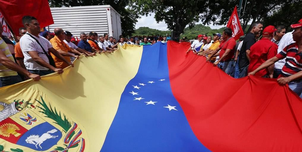 People hold a giant national flag of Venezuela during a demonstration to support Venezuelan President Nicolas Maduro's government in Caracas, Venezuela, on May 31, 2016.