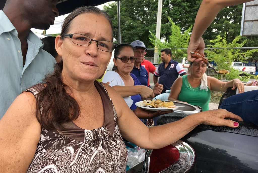"""""""It gives us lots of joy and happiness to cook ... for them,"""" says Deborah Jiménez, who leads the volunteer cooking crew. Photo Rolando Arrieta/NPR"""