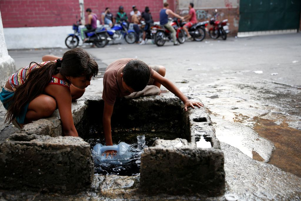 Children fill plastic containers with water from a well on a street, close to a neighbourhood called