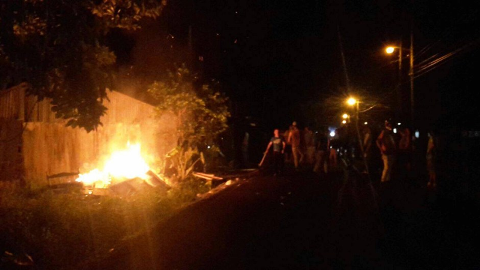 Residents blocked the street to impede fire trucks, who reported the house engulfed in flames by the tine they could reach it