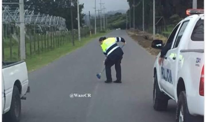 A police official cleaning the road way strewn with nails and screws. Suspected are the protesting taxi drivers. Photo from Waze