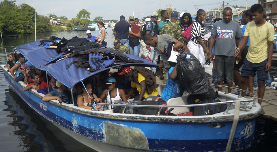 Cuban and Haitian migrants board a boat to Capurgana, on the Caribbean Gulf of Uraba (northwestern Colombia) to enter illegally into Panama through the jungle, on Saturday 6 August. (AFP)