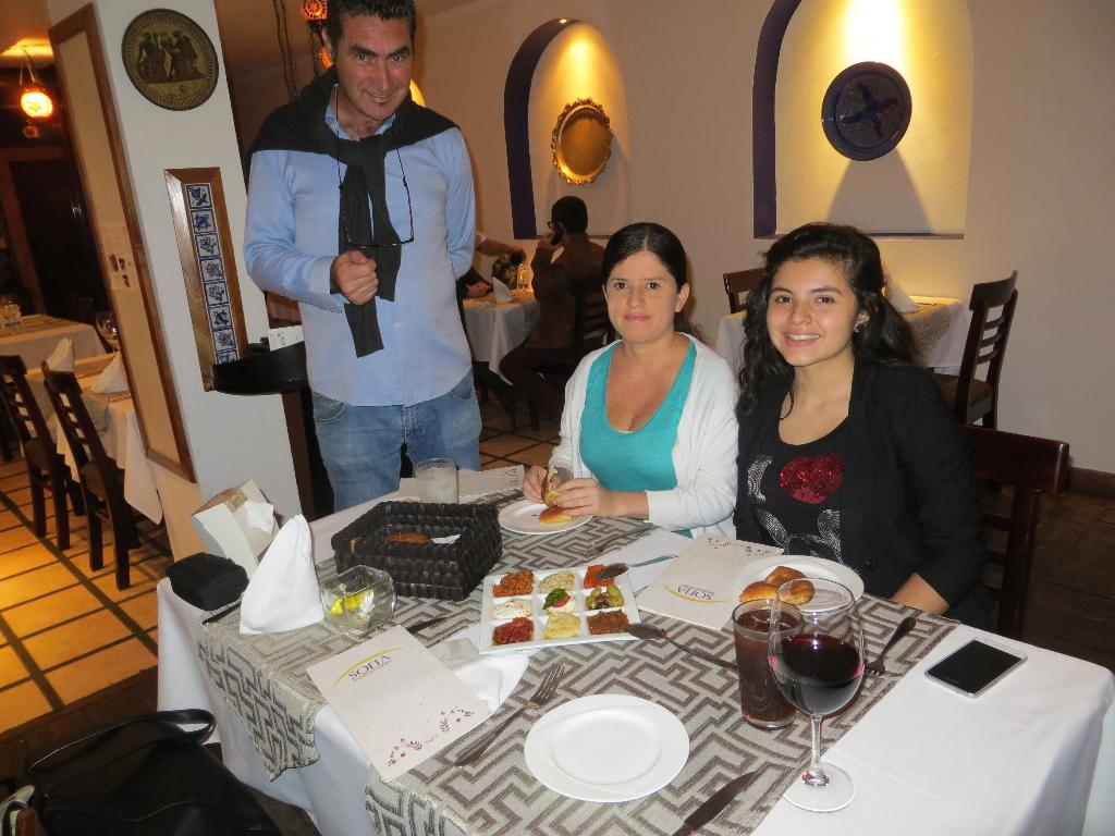 Co-owner of Sofia Mediterráneo, Mehmet Onurlap, explains the different appetizer spreads to San José guide, Nury Mora-Vargas and her daughter, Maria José.