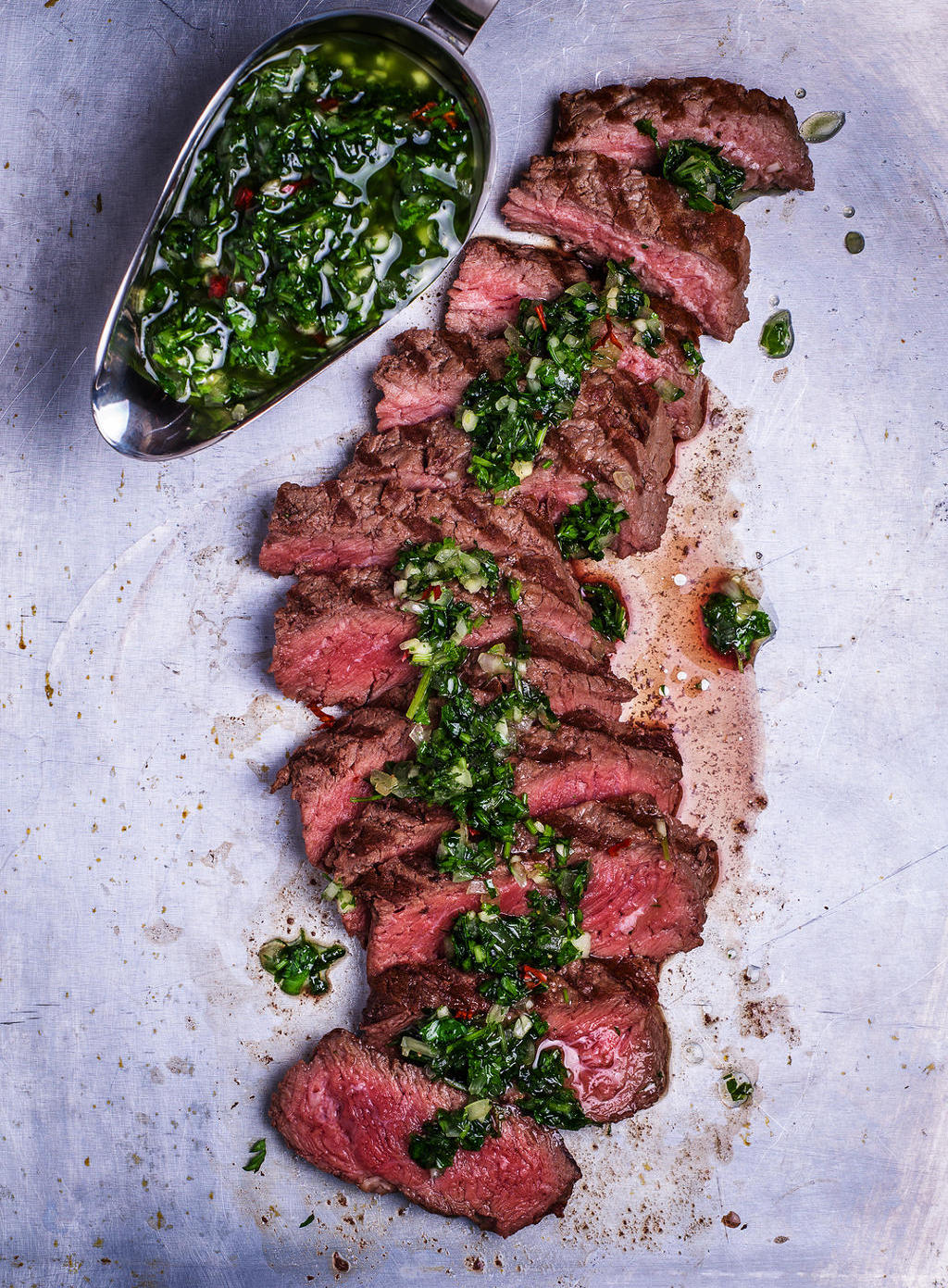 Sliced beef barbecue steak with chimichurri sauce top view rustic metal background