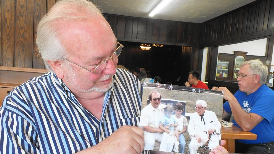 Joe Ledington of Corbin, Ky., displays a 1980s photo of him with his uncle, Colonel Harland Sanders, who perfected his world-famous Kentucky Fried Chicken in his Corbin cafe. The photo is part of a family album.