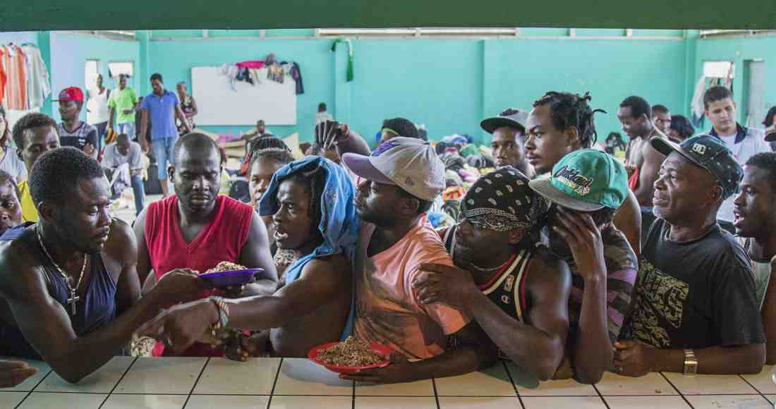 Dozens of Haitians crowd along a small breakfast table to secure a plate of beans and rice with shredded meat. Photos by Ariana Crespo