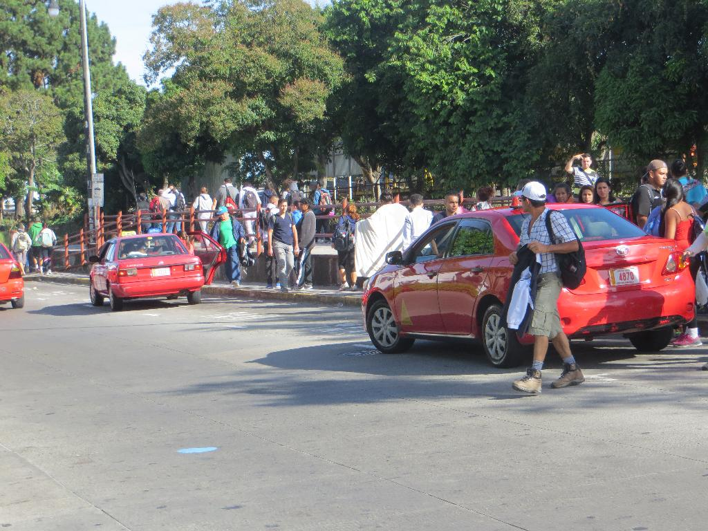 Passengers from Cartago scramble for taxis, or load onto city buses to continue their journey home.
