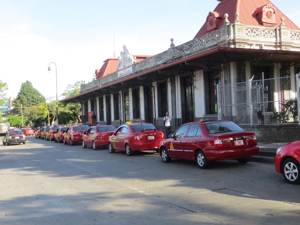 Dozens of taxis line up to await the next train-load of pilgrims returning to Downtown San José from Cartago.
