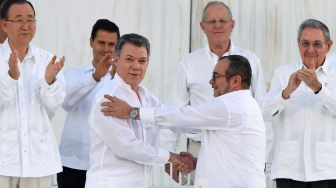 Colombia's President Santos, left, and the rebel leader known as Timochenko shook hands after signing the deal