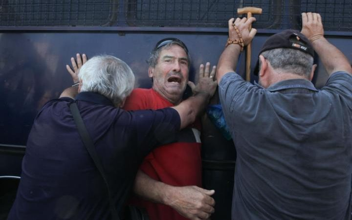 Pensioners rock a police bus that blocked their protest Credit: ALAMY