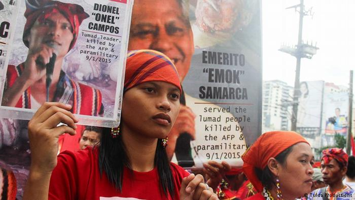 Michelle Campos holds a picture of her father, who was publicly executed for opposing mining in Mindanao, Philippines