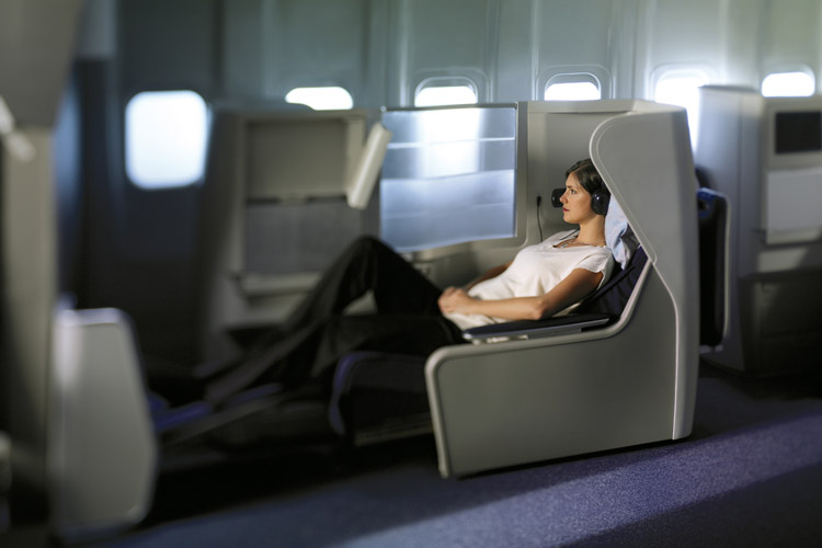 Woman reclining in spacious seat, which converts into a fully flat bed
