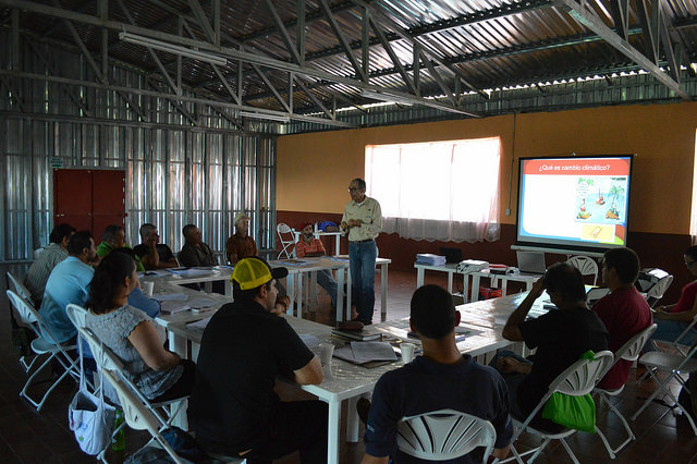 Farmers listen to Elías de Melo's presentation, at the Llano Bonito Community Centre in León Cortés, Costa Rica, in a workshop aimed at training them in the adaptation of their coffee plantations to the raise in temperatures. Credit: Diego Arguedas Ortiz/IPS