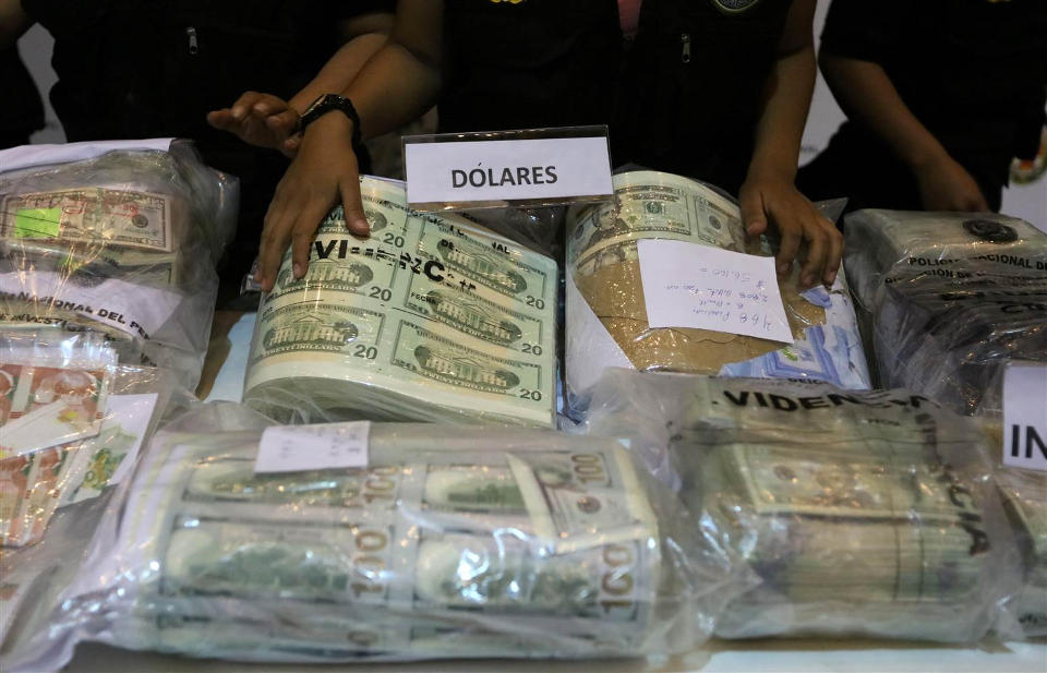 Police officers display seized counterfeit U.S. and Nuevos Soles bills at a news conference in Lima, Peru, November 16, 2016. The National Police seized $30 million worth of counterfeit bills, according to a police media release. GUADALUPE PARDO / Reuters