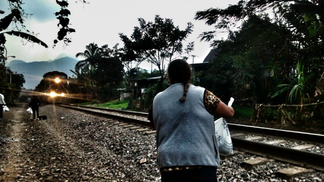 """A member of the migrant aid group """"Las Patronas"""" waits for the train known as """"The Beast"""", that was used by undocumented migrants to cross southern Mexico, to give them water and food. The Mexican government shut down the notorious train in August. Credit: Courtesy of the Mesoamerican Migrant Movement"""