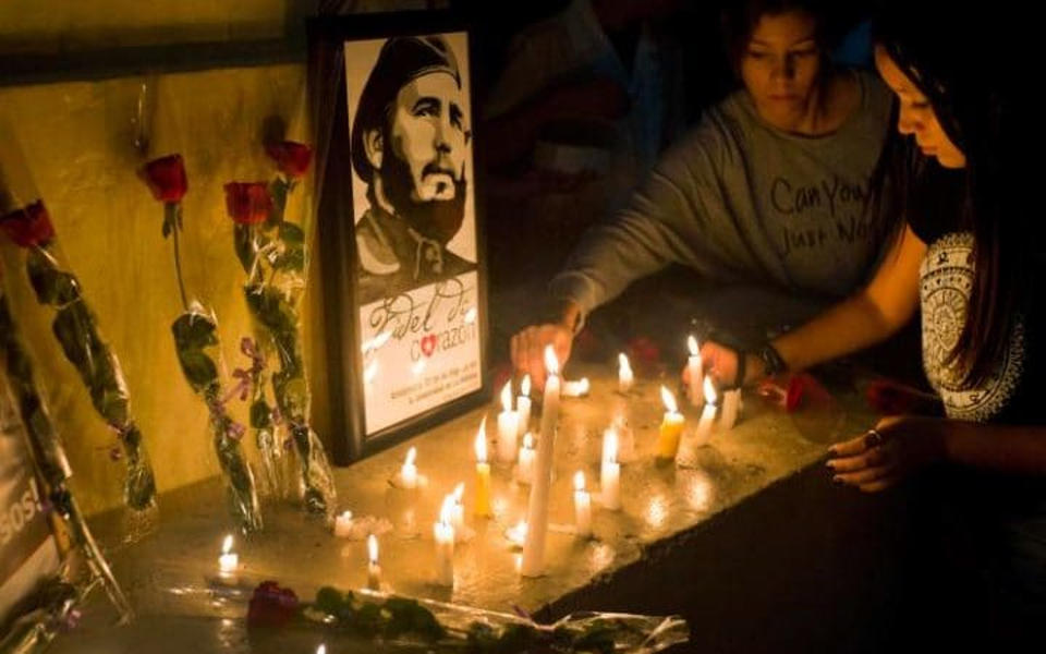 Students place candles around an image of the late Cuban leader Fidel Castro, at the university where Castro studied law Credit: Ramon Espinosa
