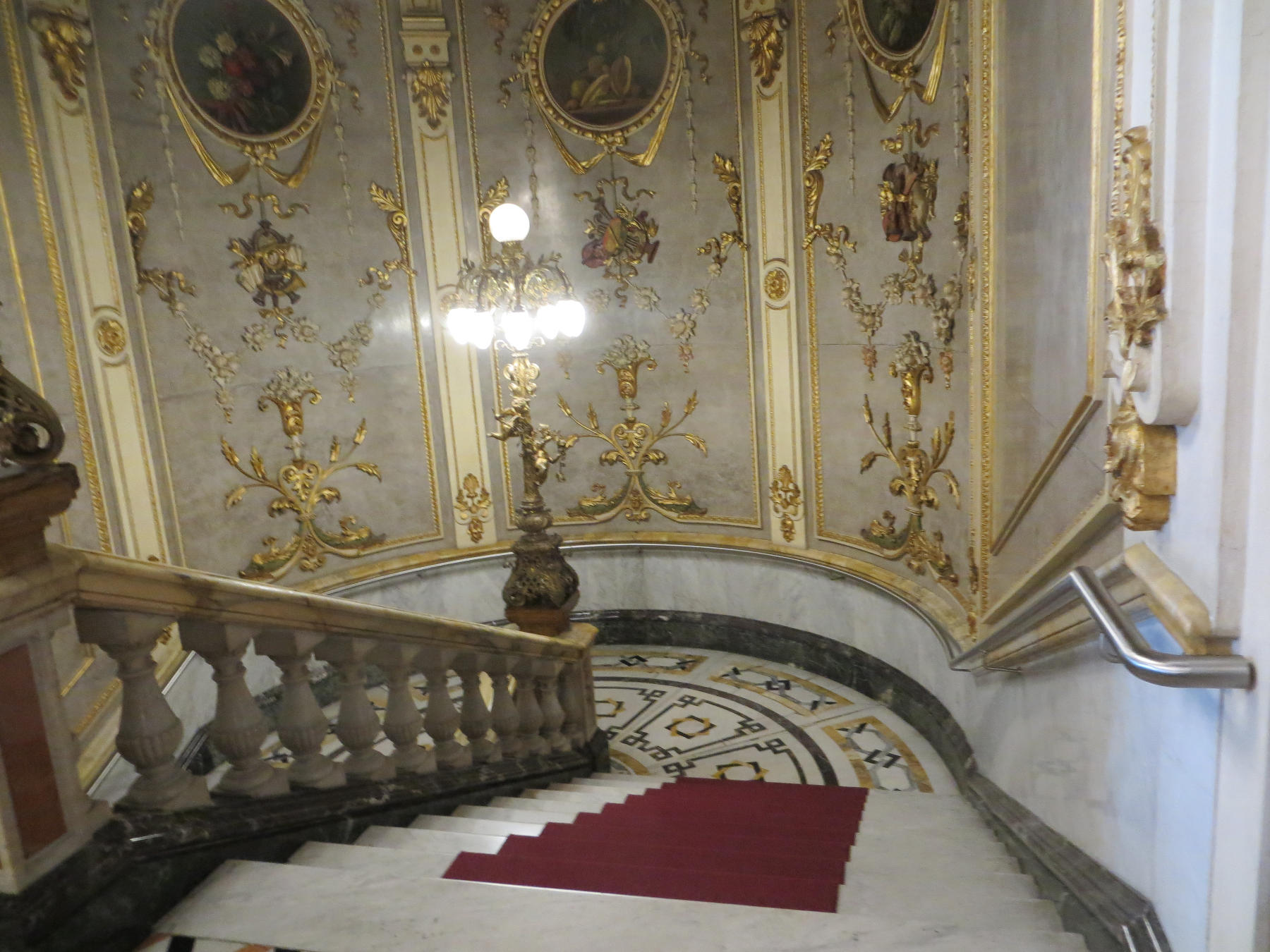 Ornate marble staircases are decorated with paintings and gold leaf detail.