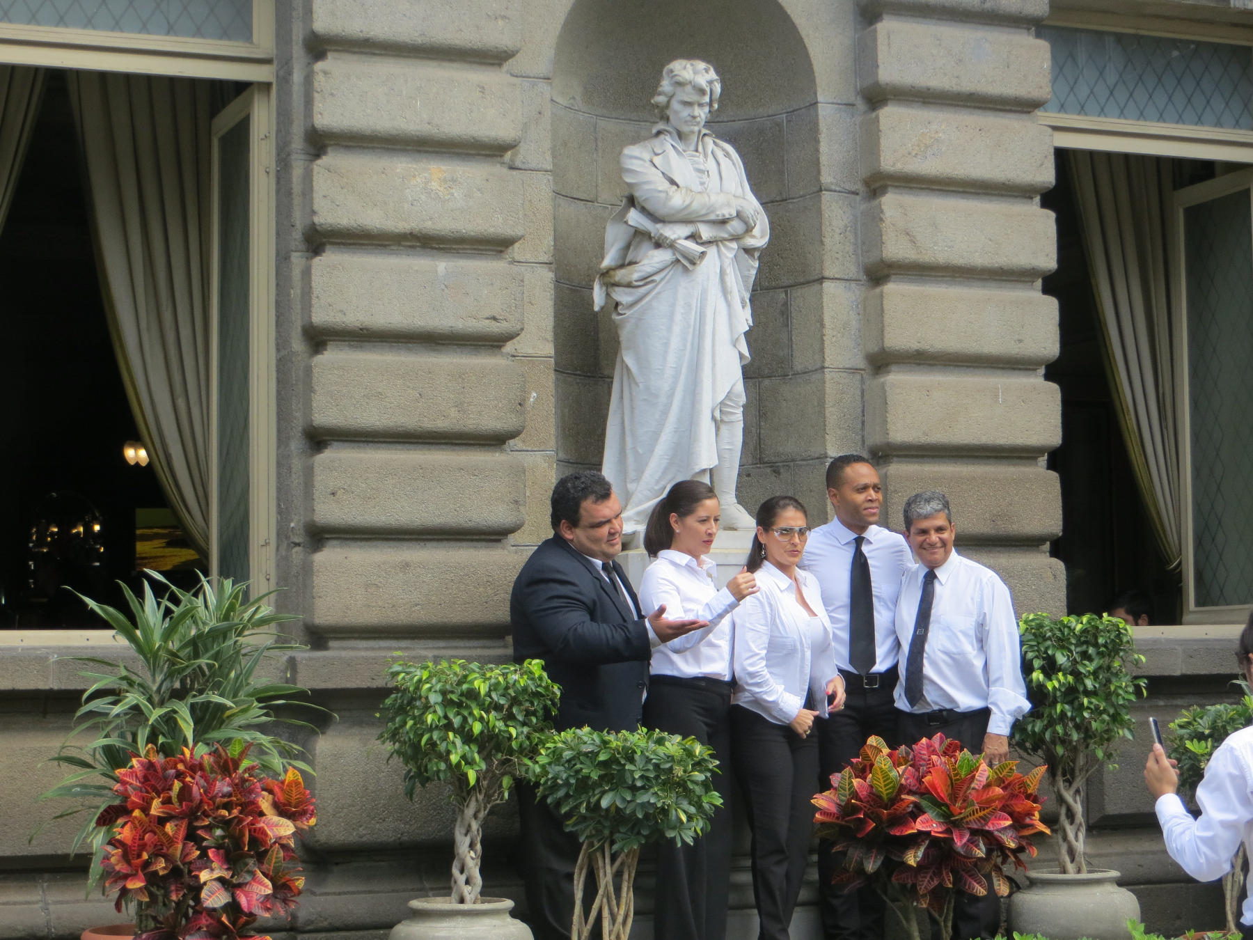 Members of the Costa Rican National Symphony Orchestra pose in front of a statue of Ludwig von Beethoven.