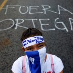 """A demonstrator stands next to a graffiti that reads """"Ortega Out"""" during a protest march against Nicaraguan President Daniel Ortega's government in Managua"""