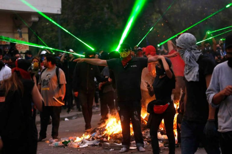 Protesters use laser pens to send police drone crashing to the ground in Chile