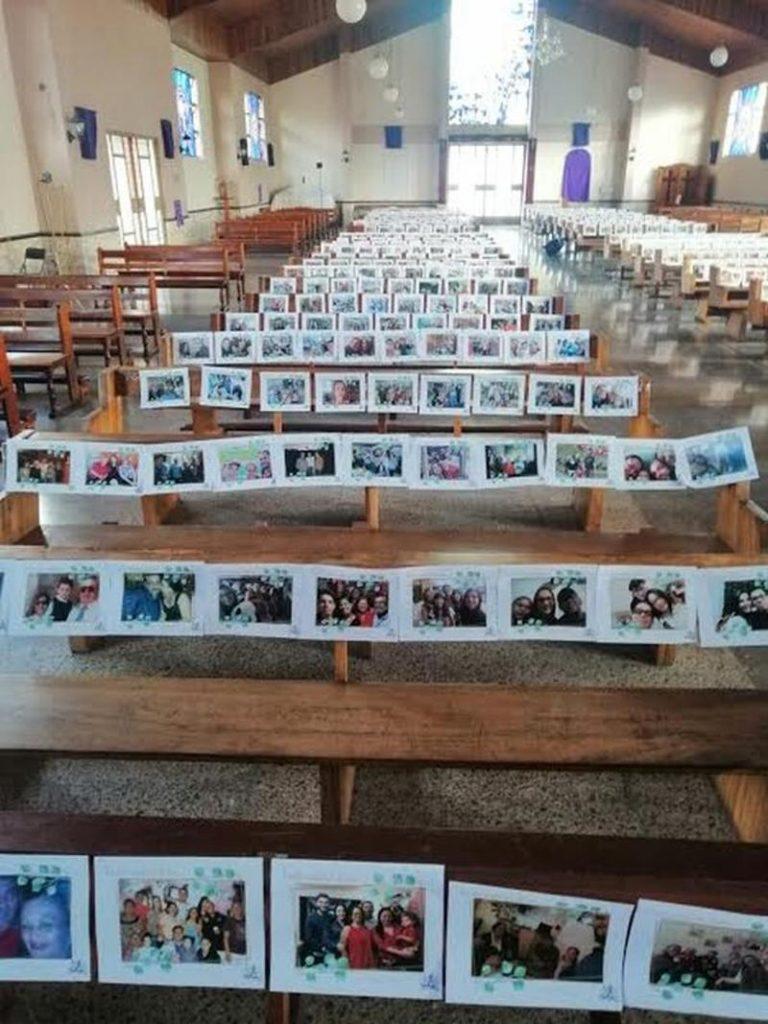 Priest celebrates mass with pews full of photos of parishioners